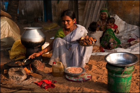 An Indian woman cooking a fish curry in the village of Malpe.